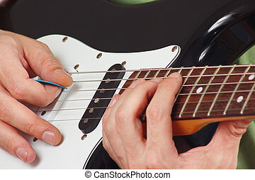 Rock guitarist put fingers for chords on electric guitar ...