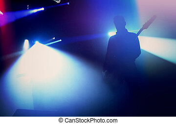 Rock guitarist silhouette on stage at concert.