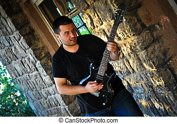 Rock guitarist - Young man playing guitar in front of the...