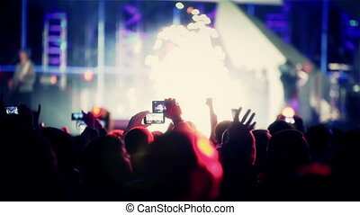 Rock heavy metal band on open air live music show cheering crowd in illumination