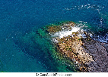 Rock in deep clean sea water. Seascape of Lloret de Mar shore, Spain.
