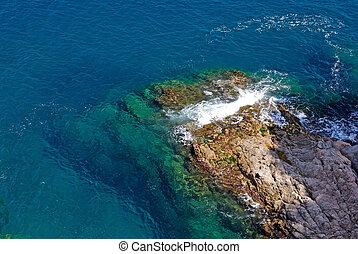 Rock in deep clean sea water. Seascape of Lloret de Mar shore, Spain.