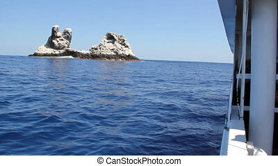 Rock in middle of ocean view from yacht in Pacific ocean....
