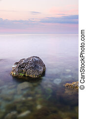 Rock in sea on sunset.