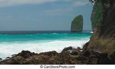 Rock in Tembeling Coastline. Ocean Waves moving toward the...