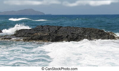 Rock in the middle of the sea waves, deep blue water surface with nice white waves