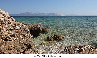 Rock is sticking out above the shoal water, above the sea...