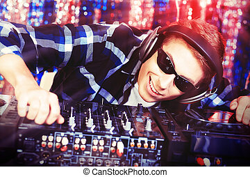 rock music - DJ mixing up some music. Disco lights in the...