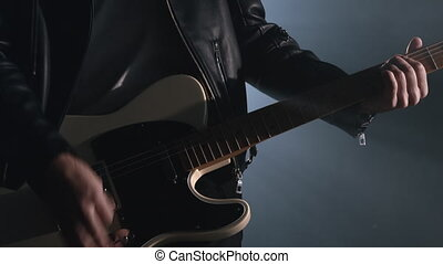 Rock musician man in smoky studio or on stage masterfully playing white electric guitar. Close up view of unrecognizable guitarist in dark room. Slow motion 4K.