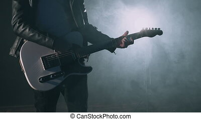 Rock musician man in smoky studio or on stage masterfully playing white electro guitar. Close up view of unrecognizable guitarist in dark room. Slow motion 4K