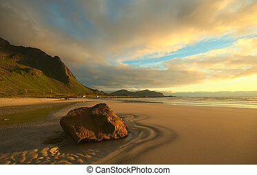 Rock on a sandy beach on the island of Flakstadoya, Lofoten, Norway lit by the yellow midnight sun in July