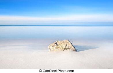 Rock on a white sand beach and sea on horizon.