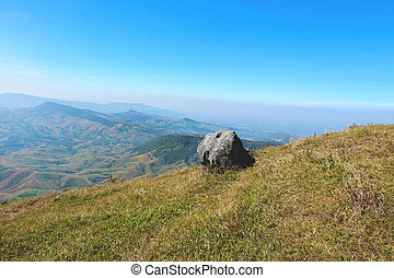 Rock on hill with mountain and blue sky background / Landscape stone field