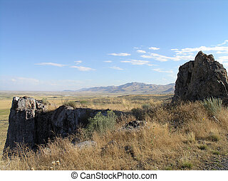 Rock outcropping with dry grass and Utah landscape in the ...
