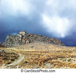 Rock over stormy sky