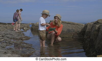 Rock Pooling - A happy young family laugh and smile together...