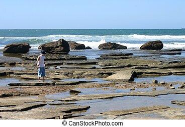 Boy walking in rock pools at low tide