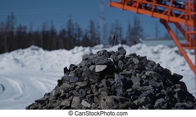 Rock pour from industrial equipment on construction site of gas plant in nature.