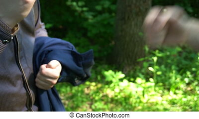 Rock, scissors, paper is played by two young man in the forest, high definition video