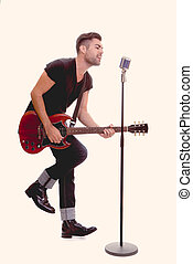 rock star singing with guitar and microphone