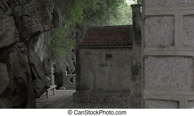 Rock with banyan tree roots and old house, Vietnam - Aged...