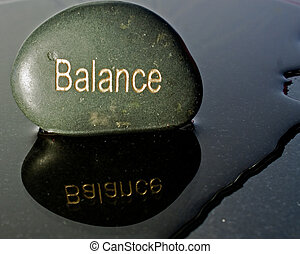 a black rock written with the word balance against a black background and a reflection