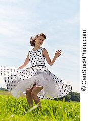 Rockabilly Girl dancing rock n roll on the meadow