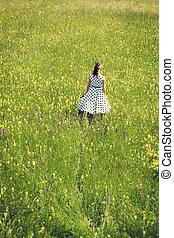 Rockabilly Girl with a white petticoat dress walking through a wildflower meadow