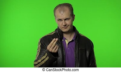 Rocker man employee asking for salary increase, smiling to camera and showing money gesture, needs more cash, financial reward, credit, loan. Portrait of guy biker posing on chroma key background
