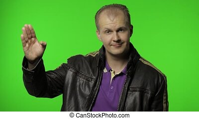 Handsome rocker man in leather jacket saluting with hand, saying yes sir and looking at camera with humorous mockery expression, pretending to listen order. Guy biker on chroma key background