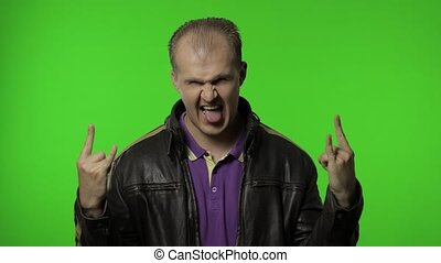 Happy rocker man in brown leather jacket showing rock and roll sign, devil horns gesture and looking with crazy expression. Portrait of guy biker posing on chroma key background. People emotions