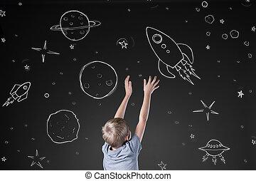 Rocket in drawn space - Little boy reaching for rocket in...