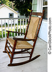 Rocking chair - A rocking chair on a white wooden porch. ...