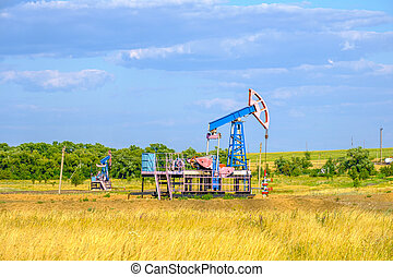 Rocking chair for oil extraction in the arid steppe on a sunny day against the blue sky. Industrial oil production.