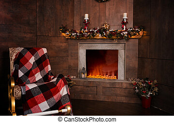 Rocking chair in the living room with decorated flaming fireplace