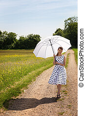 Rock'n'roll Girl with a sunshade walking on a path in the nature