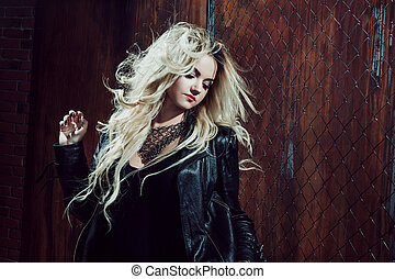 Rock'n'roll girl, young beautiful woman dances in dark...