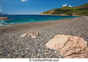 Rocks and pebble beach at Plage de Bussaglia against a turquoise sea with maquis covered rocks and clouds in background