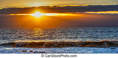 Rocks and rough sea at sunset