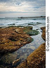 Rocks and the fishing pier in Ocean Beach, California.