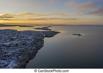 Rocks at the shore in sunset drone photo