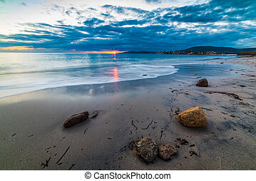 Rocks by the sea in Alghero shore at sunset