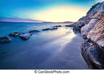 Rocks by the shore in Alghero at sunset