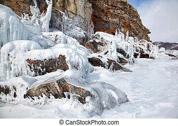Rocks covered by ice on winter siberian Baikail lake under blue sky backgroun