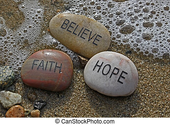 faith, hope, believe rocks in the water being washed over by a wave.
