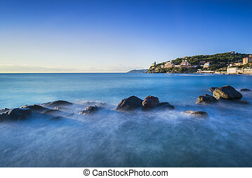Rocks in a blue ocean on sunset. Castiglioncello, Tuscany Italy