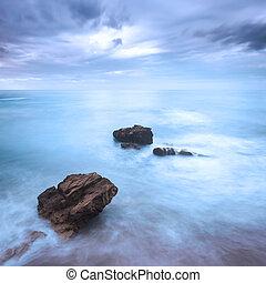 Rocks in a ocean waves under cloudy sky. Bad weather. -...