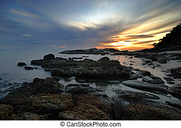 rocks in calm sea with beautiful sunrise background