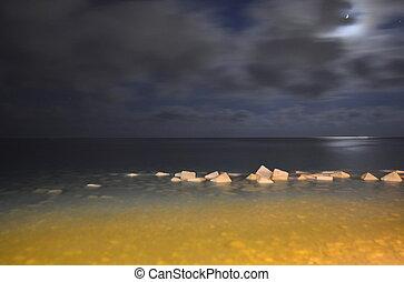 Rocks in sea by night