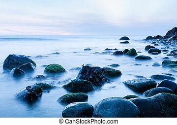 Bray Head rocks in the Irish Sea early morning cool blue long exposure image